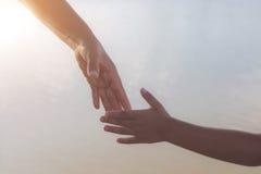 Ciérrese para arriba de las manos de la madre o de una más vieja hermana y de un niño en la puesta del sol con el espacio de la c Imagen de archivo libre de regalías