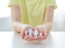 Ciérrese para arriba de las manos de la muchacha con el recorte de papel de la familia fotografía de archivo libre de regalías