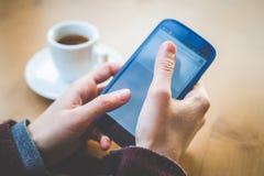 Ciérrese para arriba de las manos de la mujer con café del smartphone Imágenes de archivo libres de regalías