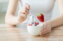 Ciérrese para arriba de las manos de la mujer con el yogur y las bayas fotografía de archivo