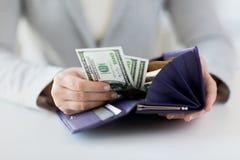Ciérrese para arriba de las manos de la mujer con la cartera y el dinero Imagenes de archivo