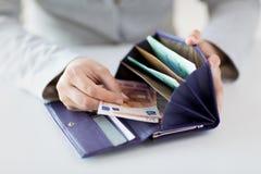 Ciérrese para arriba de las manos de la mujer con la cartera y el dinero del euro Imagen de archivo