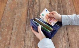 Ciérrese para arriba de las manos de la mujer con la cartera y el dinero del euro Fotos de archivo libres de regalías