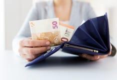 Ciérrese para arriba de las manos de la mujer con la cartera y el dinero del euro Fotografía de archivo libre de regalías
