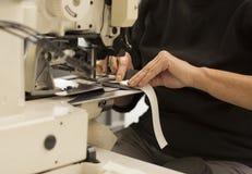 Ciérrese para arriba de las manos de la mujer que actúan una máquina de coser Imagen de archivo