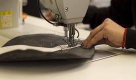 Ciérrese para arriba de las manos de la mujer que actúan una máquina de coser Imagen de archivo libre de regalías
