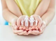 Ciérrese para arriba de las manos de la mujer y de la muchacha con la familia de papel Imagen de archivo