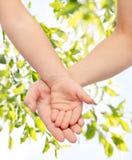 Ciérrese para arriba de las manos de la mujer y del pequeño niño junto Fotos de archivo libres de regalías