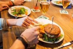 Ciérrese para arriba de las manos de los amigos que comparten la hamburguesa en la barra Fotografía de archivo libre de regalías