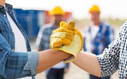 Ciérrese para arriba de las manos de los constructores que hacen el apretón de manos foto de archivo
