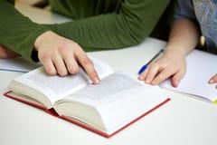 Ciérrese para arriba de las manos de los estudiantes con el libro o el libro de texto Imagenes de archivo