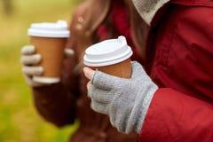 Ciérrese para arriba de las manos de los pares con café en otoño Fotografía de archivo
