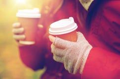 Ciérrese para arriba de las manos de los pares con café en otoño Foto de archivo