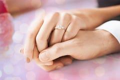 Ciérrese para arriba de las manos de los pares con el anillo de compromiso Fotos de archivo