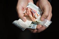 Ciérrese para arriba de las manos del adicto con las drogas y el dinero Foto de archivo