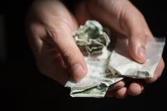Ciérrese para arriba de las manos del adicto con las drogas y el dinero Fotos de archivo