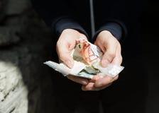 Ciérrese para arriba de las manos del adicto con las drogas y el dinero Imagen de archivo