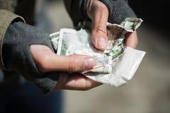 Ciérrese para arriba de las manos del adicto con las drogas y el dinero Imagenes de archivo