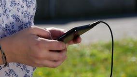 Ciérrese para arriba de las manos del adolescente con un smartphone