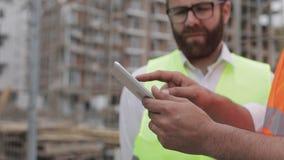 Ciérrese para arriba de las manos del arquitecto usando la tableta cerca de emplazamiento de la obra El hombre del constructor y  almacen de metraje de vídeo