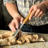 Ciérrese para arriba de las manos del carpintero que trabajan con el cortador Imagen de archivo libre de regalías