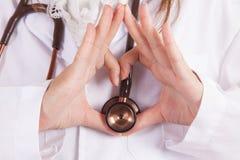 Ciérrese para arriba de las manos del doctor que hacen forma del corazón fotografía de archivo libre de regalías