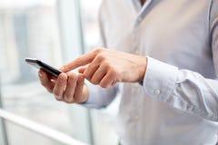 Ciérrese para arriba de las manos del hombre con smartphone en la oficina fotografía de archivo libre de regalías
