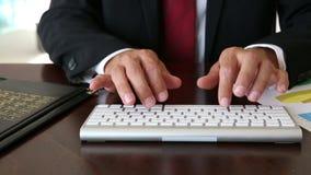 Ciérrese para arriba de las manos del hombre de negocios que mecanografían en el teclado almacen de video