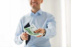 Ciérrese para arriba de las manos del hombre de negocios que sostienen el dinero Foto de archivo libre de regalías