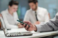 Ciérrese para arriba de las manos del hombre de negocios usando el teléfono elegante en la reunión Imagenes de archivo
