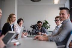 Ciérrese para arriba de las manos del hombre de negocios usando la tableta en la reunión imagen de archivo