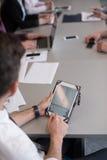 Ciérrese para arriba de las manos del hombre de negocios usando la tableta en la reunión fotos de archivo libres de regalías