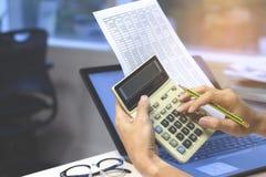 Ciérrese para arriba de las manos del hombre de negocios o del contable que sostienen la calculadora fotos de archivo
