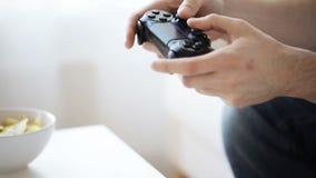 Ciérrese para arriba de las manos del hombre que juegan al videojuego en casa metrajes