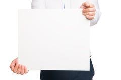 Ciérrese para arriba de las manos del hombre que muestran al tablero en blanco blanco imagen de archivo