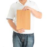 Ciérrese para arriba de las manos del hombre que muestran al tablero en blanco de madera Fotografía de archivo libre de regalías
