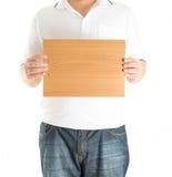Ciérrese para arriba de las manos del hombre que muestran al tablero en blanco de madera Fotos de archivo libres de regalías