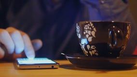 Ciérrese para arriba de las manos del hombre usando el smartphone para la mensajería El teléfono descansa sobre una tabla y está  metrajes