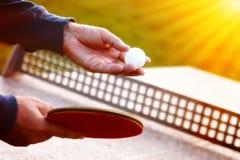 Ciérrese para arriba de las manos del jugador de tenis con la estafa de tenis en fondo de la naturaleza en día soleado Primer tir Fotos de archivo libres de regalías