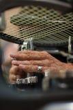 Ciérrese para arriba de las manos del larguero del tenis que hacen la encadenación de la estafa Imagen de archivo