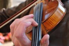 Ciérrese para arriba de las manos del músico en el cuello del violín Imagenes de archivo