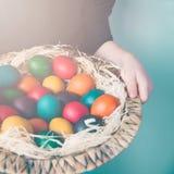 Ciérrese para arriba de las manos del niño que sostienen una cesta de mimbre llena de huevos de Pascua coloridos Fotografía de archivo libre de regalías