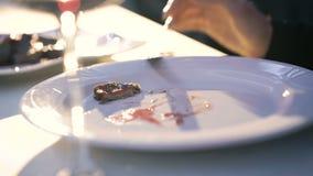 Ciérrese para arriba de las manos del ` s de la mujer que cortan el ort del plato en la placa en el restaurante 4K almacen de video