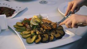Ciérrese para arriba de las manos del ` s de la mujer que cortan pescados y tajada en una placa en el restaurante 4K almacen de video