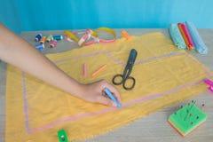 Ciérrese para arriba de las manos del ` s de la mujer que dibujan un modelo en tejido amarillo Cinta métrica y accesorios de cost Imágenes de archivo libres de regalías