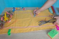 Ciérrese para arriba de las manos del ` s de la mujer que dibujan un modelo en tejido amarillo Cinta métrica y accesorios de cost Fotografía de archivo libre de regalías