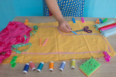Ciérrese para arriba de las manos del ` s de la mujer que dibujan un modelo en tejido amarillo Cinta métrica y accesorios de cost Imagen de archivo libre de regalías