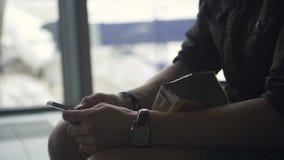Ciérrese para arriba de las manos del ` s del hombre usando smartphone móvil en aeropuerto metrajes
