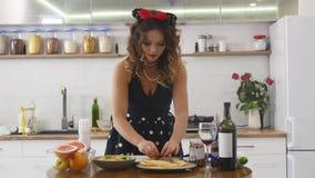 Ciérrese para arriba de las manos del ` s de la mujer que ponen el relleno en la crepe Cocinar la comida deliciosa nacional en la almacen de video