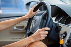 Ciérrese para arriba de las manos del ` s de la mujer que sostienen el volante imagenes de archivo